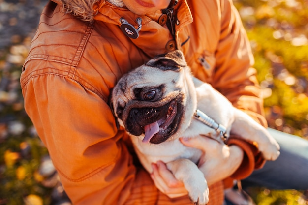 Master holding pug dog in hands in autumn park