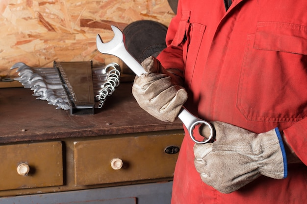 Мастер держит в руках ключи от набора ключей на верстаке с инструментами в гаражной мастерской
