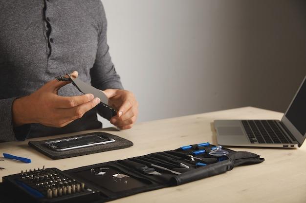 Il maestro tiene un nuovo schermo per la sostituzione sopra lo smartphone smontato nel suo laboratorio, cassetta degli attrezzi con strumenti e laptop di fronte a lui sul tavolo bianco, spazio per il testo a destra