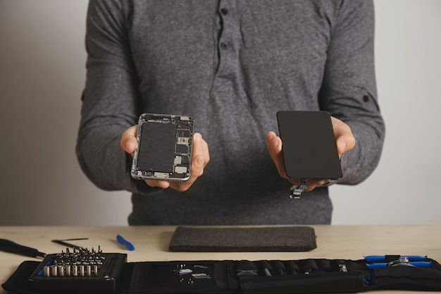 Мастер держит корпус смартфона и новый сменный экран над набором инструментов для ремонта на белом столе