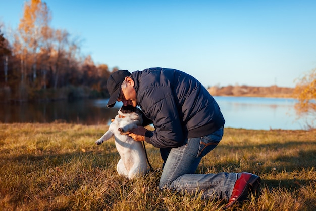 Master hugging pug dog in autumn park by river