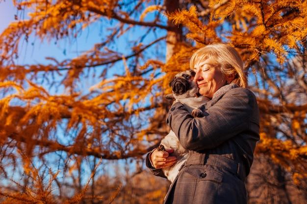 Master hugging pug dog in autumn park