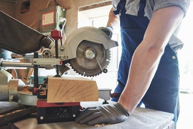 製材所でグラインダーを使用して作業服のマスター。