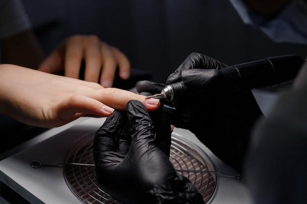 Мастер в медицинских перчатках делает маникюр в салоне красоты