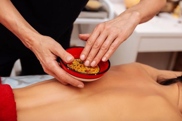 Мастер в салоне. внимательный мастер массажа окунает руку в таз со специальным маслом перед обработкой спины клиента.