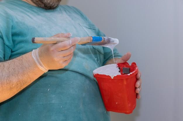 페인트와 브러시를 잡는 데 사용되는 빨간색 플라스틱 페인트 통 과정의 마스터