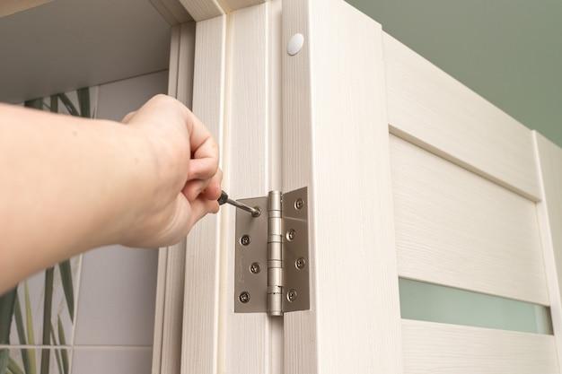 Мастер устанавливает дверь и при помощи отвертки прикручивает петлю.