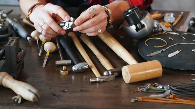 マスタージュエラーは手に工具を持ち、ジュエリーワークショップでジュエリーを作ります。