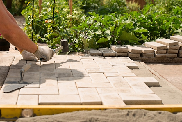 The master  lays paving stones in layer