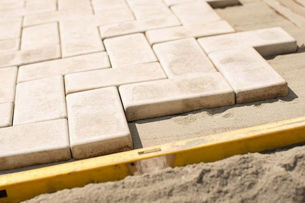 The master  lays paving stones in layers