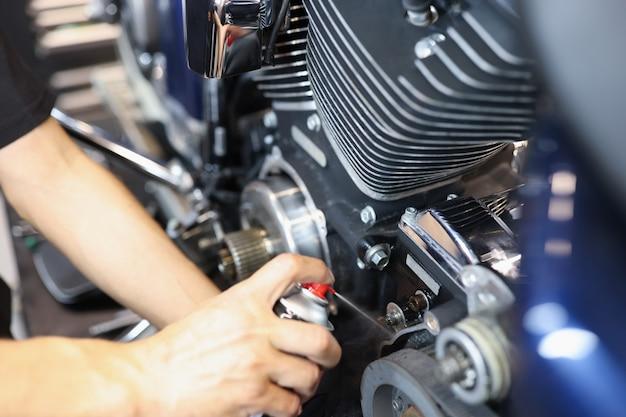 마스터 자물쇠 제조공은 차고 오토바이 유지 보수 개념에서 오토바이 엔진에 액체를 퍼프