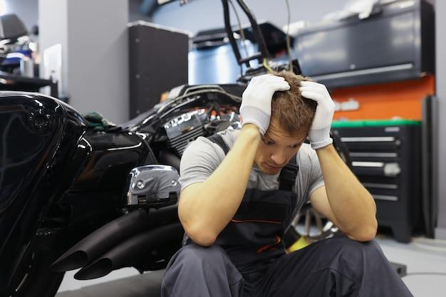 두통을 가진 마스터 자물쇠 제조공은 주유소 직장에서 오토바이 근처에 앉아 있습니다.
