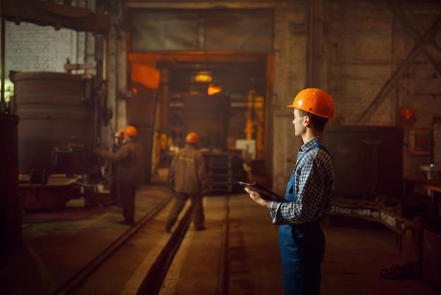 Мастер смотрит на процесс выплавки стали в печи
