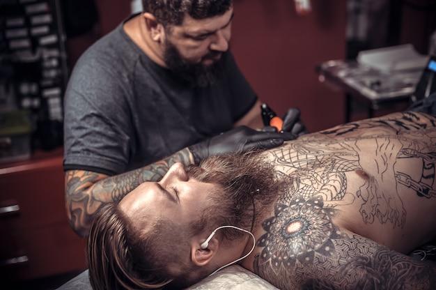 マスターはタトゥーパーラーでタトゥーを作ります。