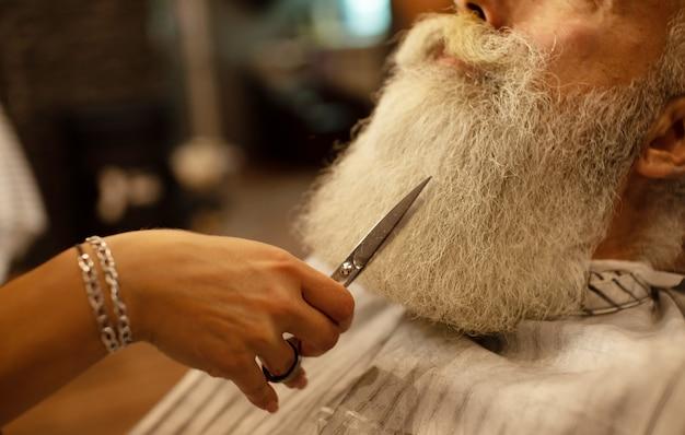 マスターは理髪店のサロンでひげを修正します。写真をクローズアップ。