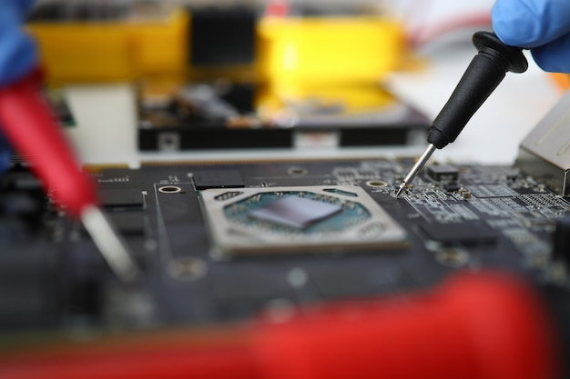 Master makes diagnostics of motherboard with tester. electronic circuit board service concept