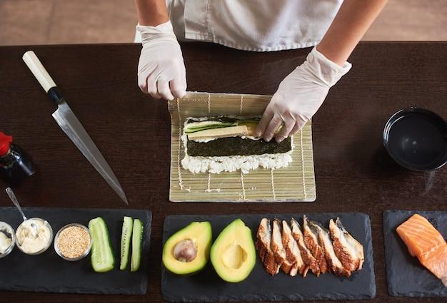 竹マットを使って海苔、ご飯、きゅうり、オムレツで巻き寿司を作るマスター