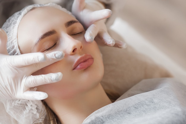 Master making a cosmetic procedure for her client. skin care treatment. woman making a face care procedure.