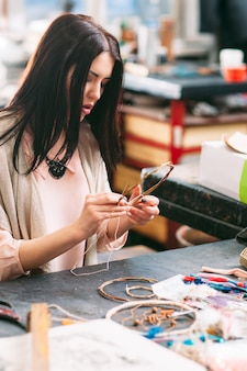 Master making dreamcatcher in art workplace