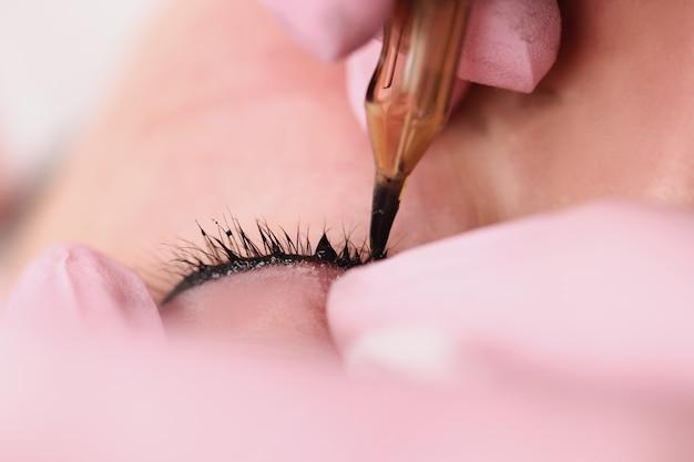 美容院のクローズアップで女性クライアントにまつげの間のスペースのアートメイクをマスター。美容サービスのコンセプト