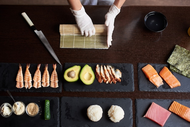 Master making a sushi roll with nori, rice, cucumber and omelet using bamboo mat. closeup view of cooking process. view from the top