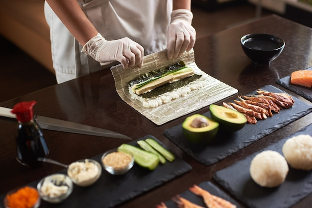 Master making a sushi roll with nori, rice, cucumber and omelet using bamboo mat