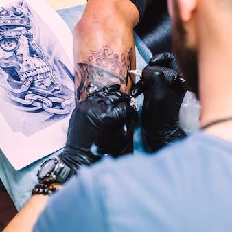 Мастер, делающий татуировку с железом