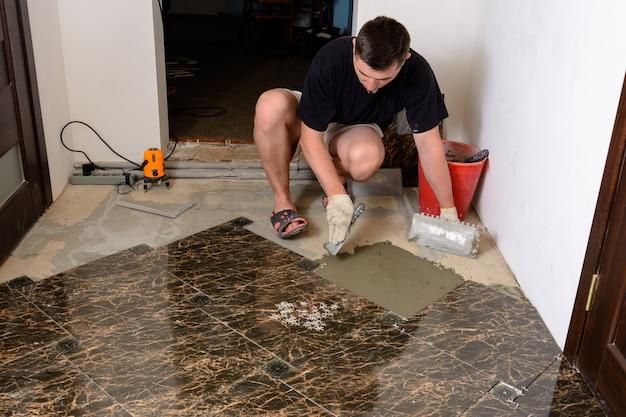 マスターマンは、大理石のタイルを敷設するために、接着剤溶液でヘラをセメント表面に押し込みます
