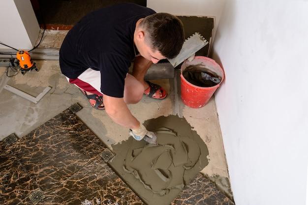 Мастер-мужчина прижимает к цементной поверхности шпатель с клеевым раствором для укладки мраморной плитки.