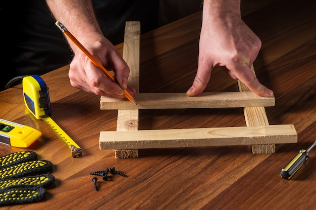 The master marks the distance on the wooden plank with a pencil. builder hands close up.