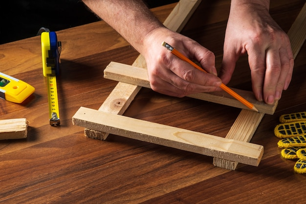 The master marks the distance on the wooden plank with a pencil.