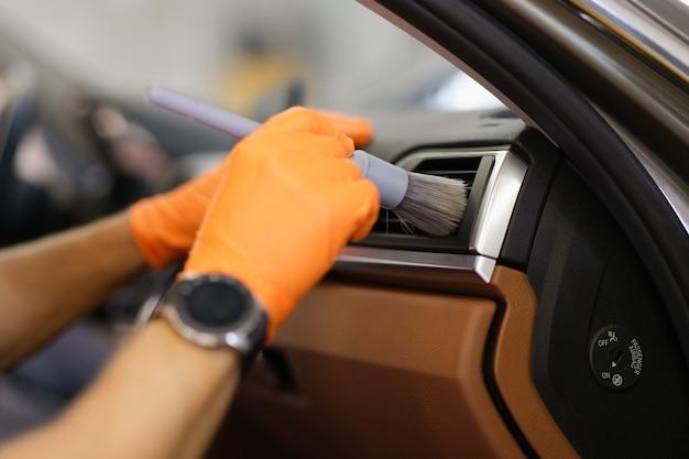 ブラシのクローズアップで車のエアコンを拭くゴム手袋のマスターメカニック