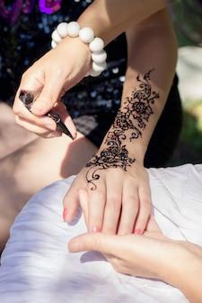 Master mehndi draws henna on a female hand