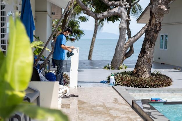 마스터 맨은 열대 호텔에서 에어컨을 청소합니다.