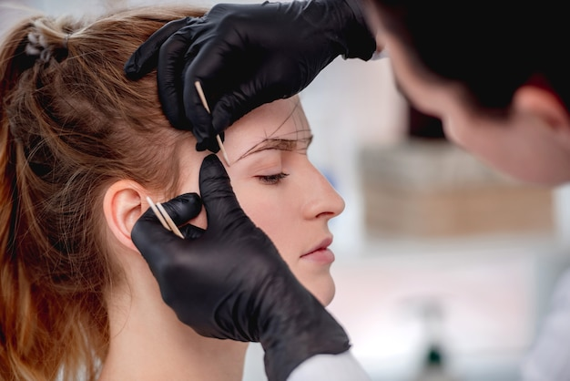 Master of microblading permanent makeup draws new shape of eyebrows for model girl.