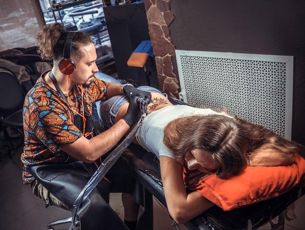 Мастер искусства татуировки, создавая татуировку на своей клиентке.