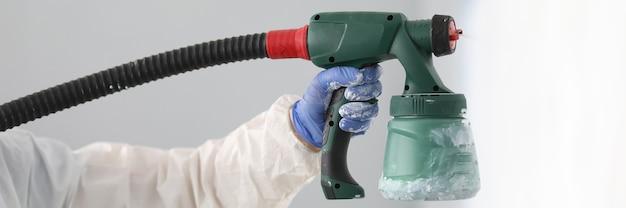 Мастер покрасить стену белой краской. мужская рука в защитном костюме держит пистолет-распылитель в руке крупным планом.