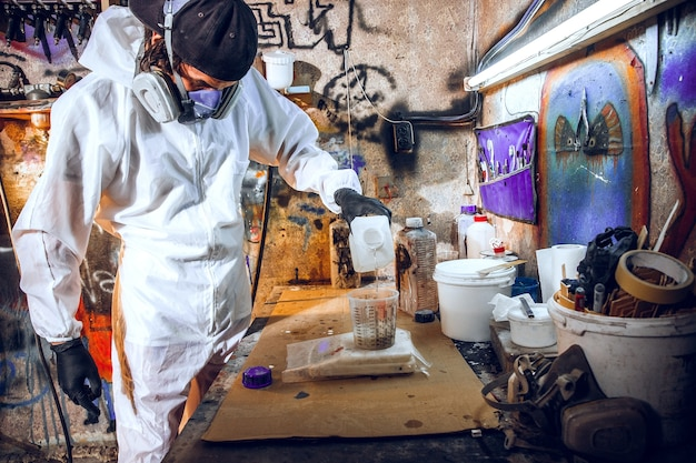 Master painter in a factory - industrial painting wood with spray gun.