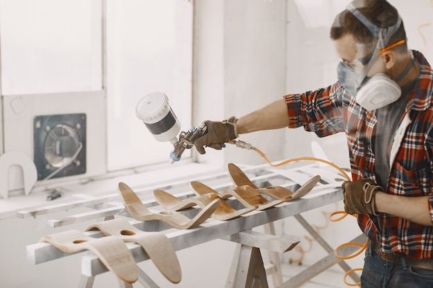 Maestro pittore in una fabbrica di pittura su legno con pistola a spruzzo