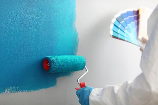 Мастер-художник держит в руках цветовую палитру с оттенками синего