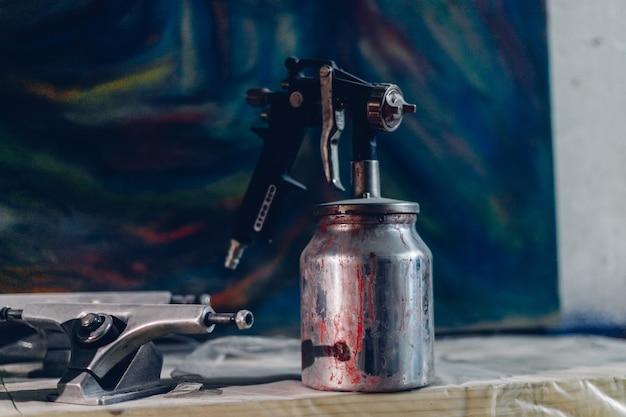공장의 마스터 화가 - 스프레이 건이 있는 산업용 페인팅 목재. 소프트 포커스입니다. 얕은 dof