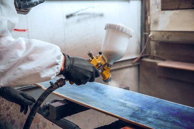Мастер-маляр на фабрике - промышленная окраска дерева с помощью краскопульта.