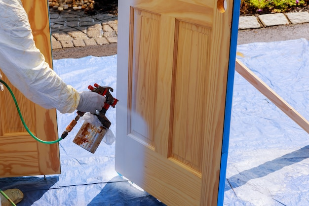 Master painting wood doors with spray gun processing painting base