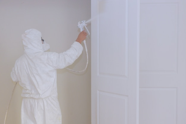 Master painting wood doors with spray gun processing painting door house