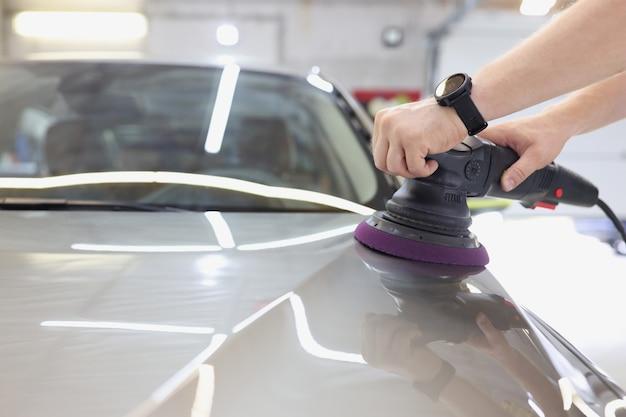 Мастер полирует кузов машины полировальной машиной, удаляя потертости и царапины на машине без