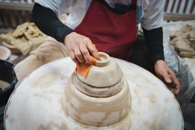 물레에 흰 점토 도자기 제품을 만드는 도예가. 손은 항아리에서 그릇을 조각합니다. 예술 창의력 문화 전통 수제 공예.