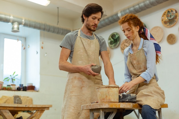 粘土を提示するマスター。設備の整ったスタジオで作業し、新鮮な粘土を保持している集中したプロのカップル