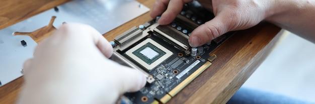 ワークショップのクローズアップでビデオカードを修理するマスター