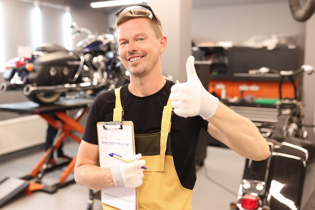 Master repairman holding clipboard with documents and showing thumb up to car workshop car
