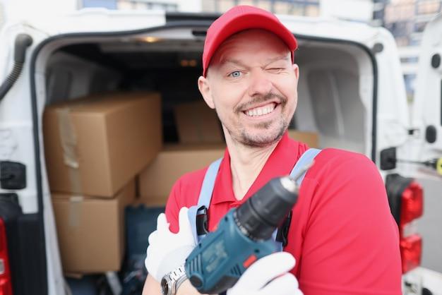 Мастер-ремонтник, держа в руках электродрель возле автомобиля